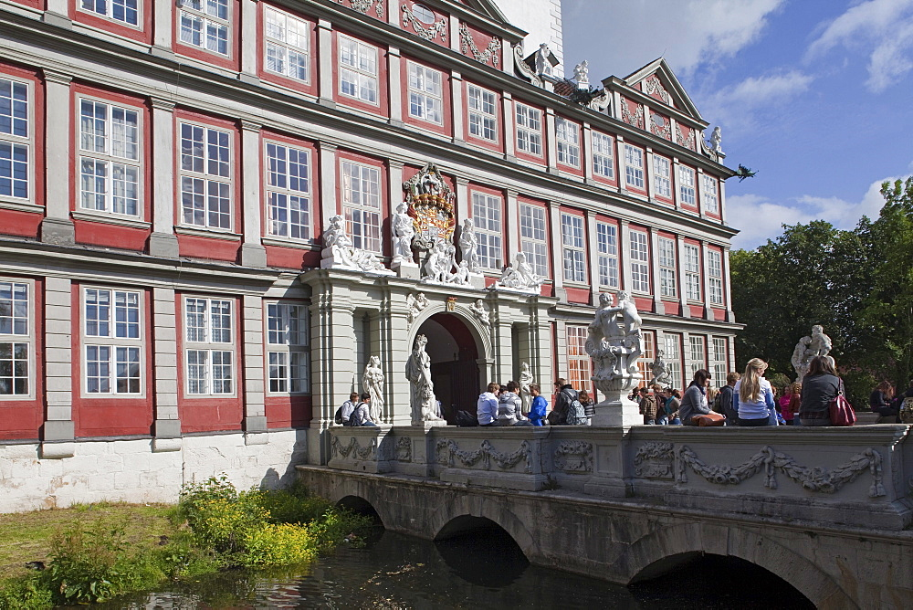 Entrance to Wolfenbuettel castle, now a secondary school, pupils sitting on the bridge, Wolfenbuettel, Lower Saxony, Germany