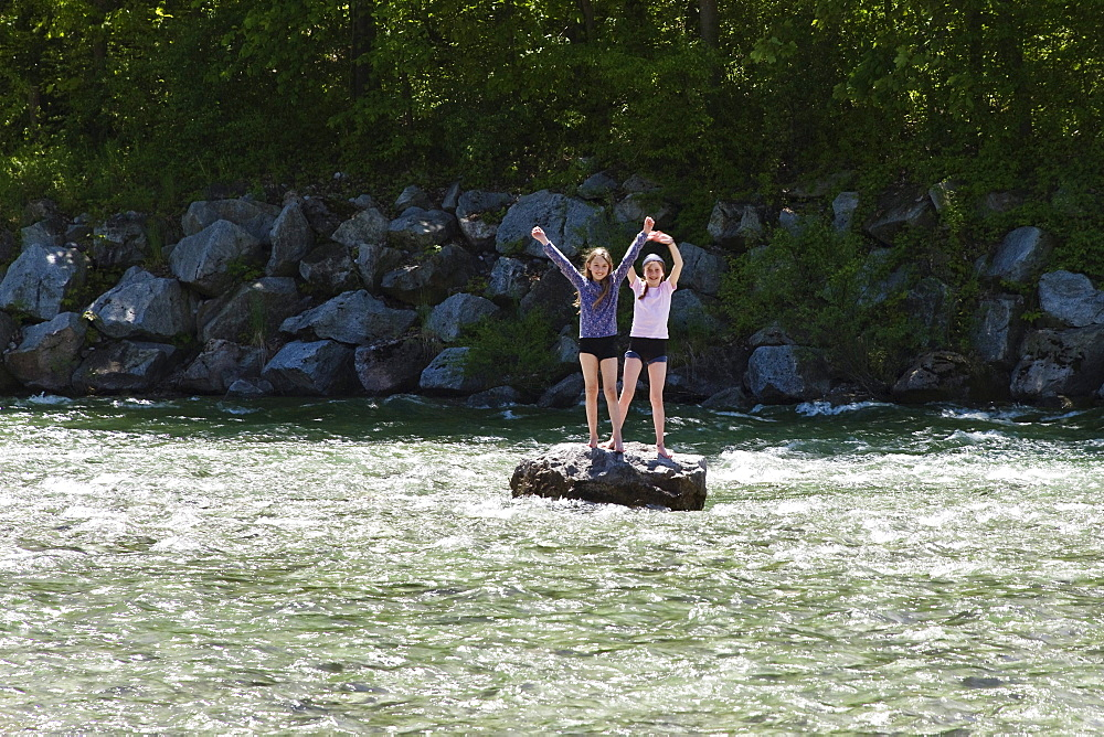 Two girls (10 years) standing on rock in river Isar, near Fleck, Isar Cycle Route, Upper Bavaria, Germany