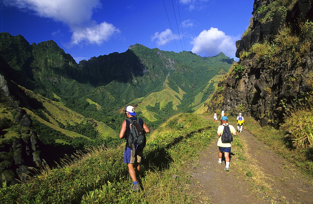 People hiking through the wild interior of the island of Fatu Iva, French Polynesia