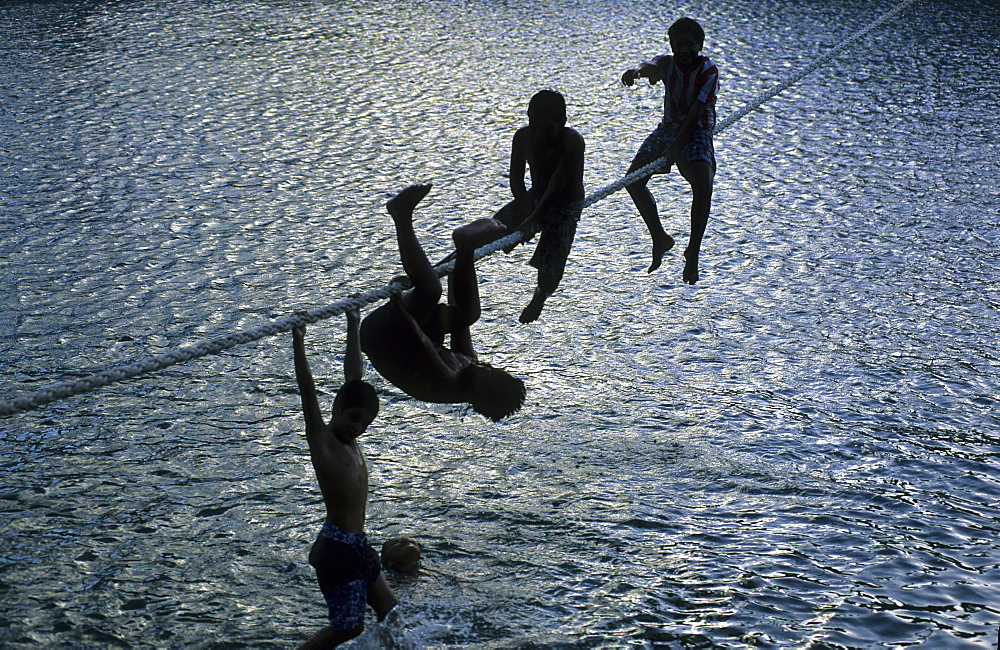Children playing on a rope in the harbour of Hakahau on the island of Ua Pou, French Polynesia