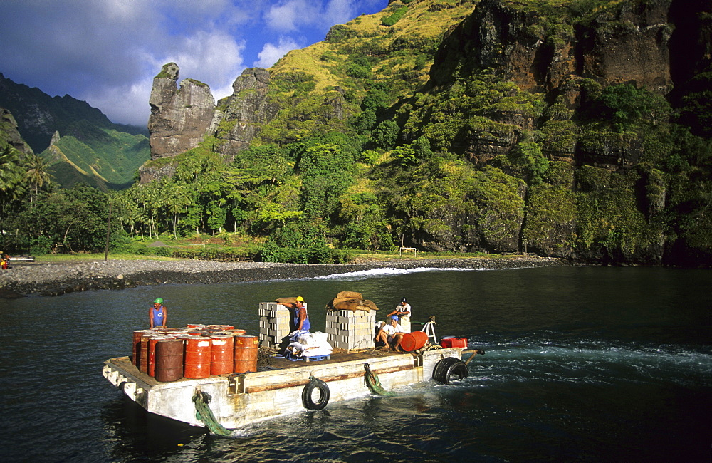 People transporting cargo on a barge in the Bay of Hanavave on the island of Fatu Iva, French Polynesia