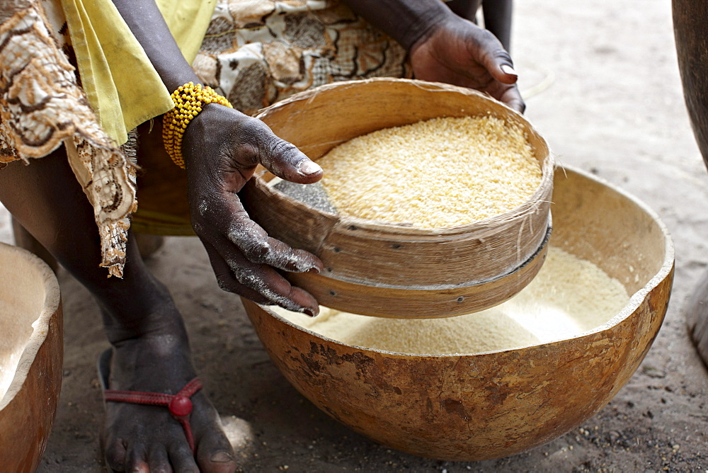 Woman sieving cornmeal, Bougouni, Mali, Africa