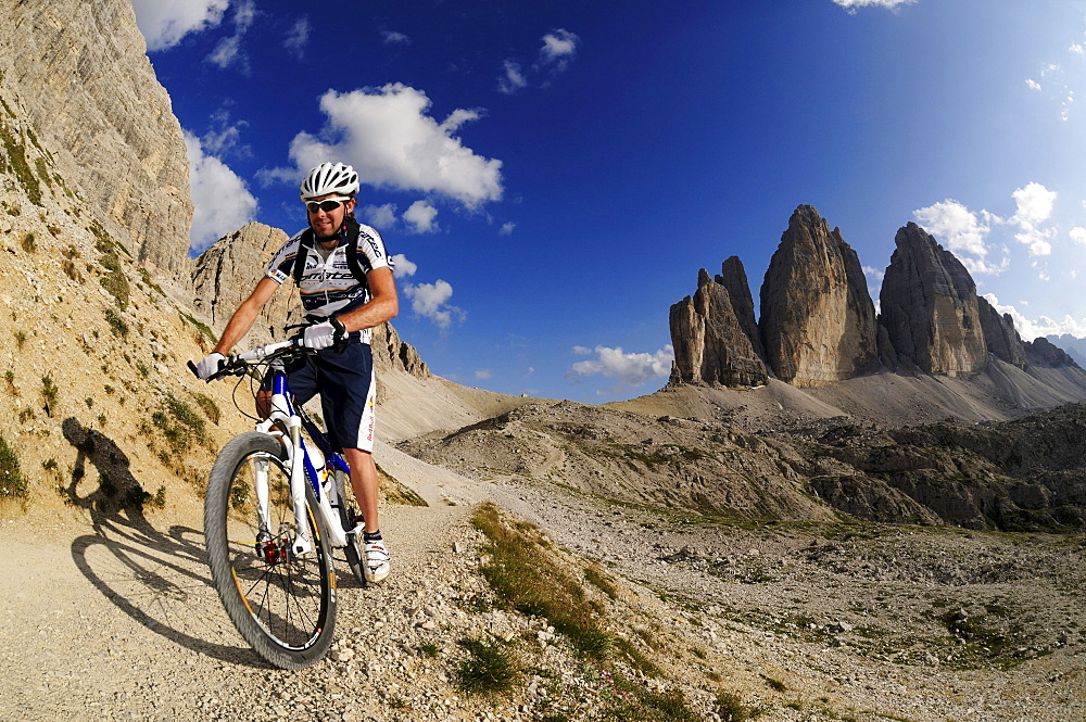Cyclist Roland Stauder in front of the Drei Zinnen, Hochpuster valley, South Tyrol, Dolomites, Italy, Europe