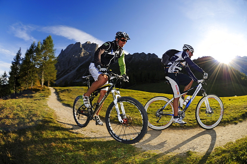People on mountain bikes at Rotwand in the sunlight, Sexten, Hochpuster valley, South Tyrol, Dolomites, Italy, Europe