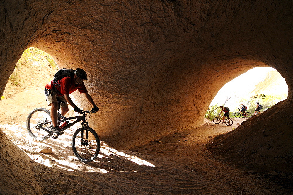 Mountainbiker in the tonnel of a river, Uchisar, Goereme, Cappadocia, Turkey