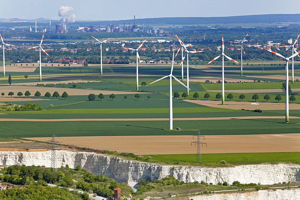 Aerial view of a wind farm, turbines in an agricultural landscape, lime pit in the foreground, steelworks in the background, Salzgitter, Lower Saxony, Germany