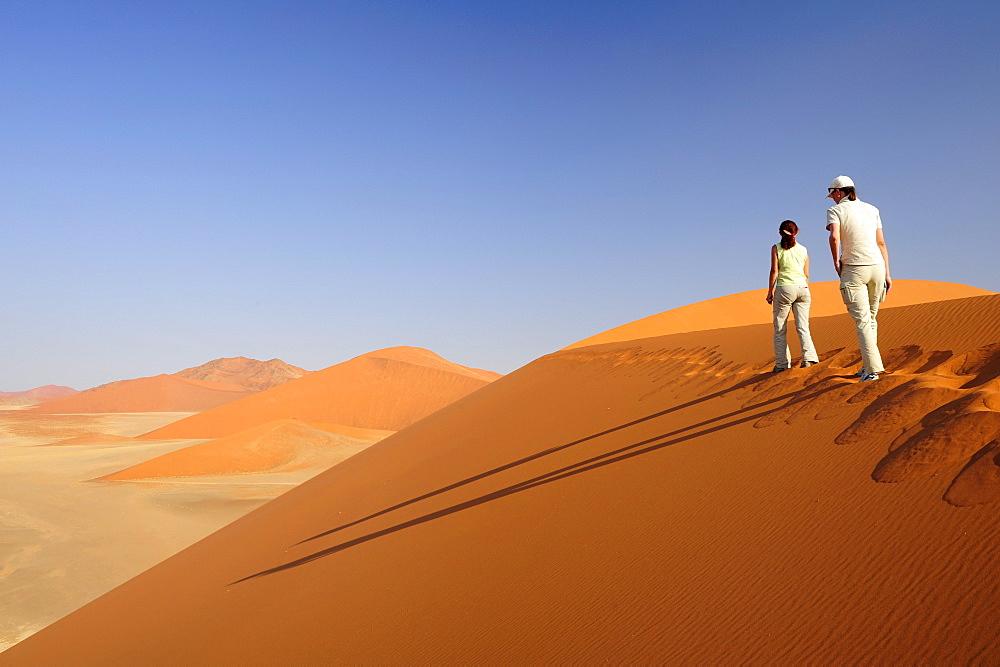 Two women walking on red sand dune in Sossusvlei, dune 45, Sossusvlei, Namib Naukluft National Park, Namib desert, Namib, Namibia