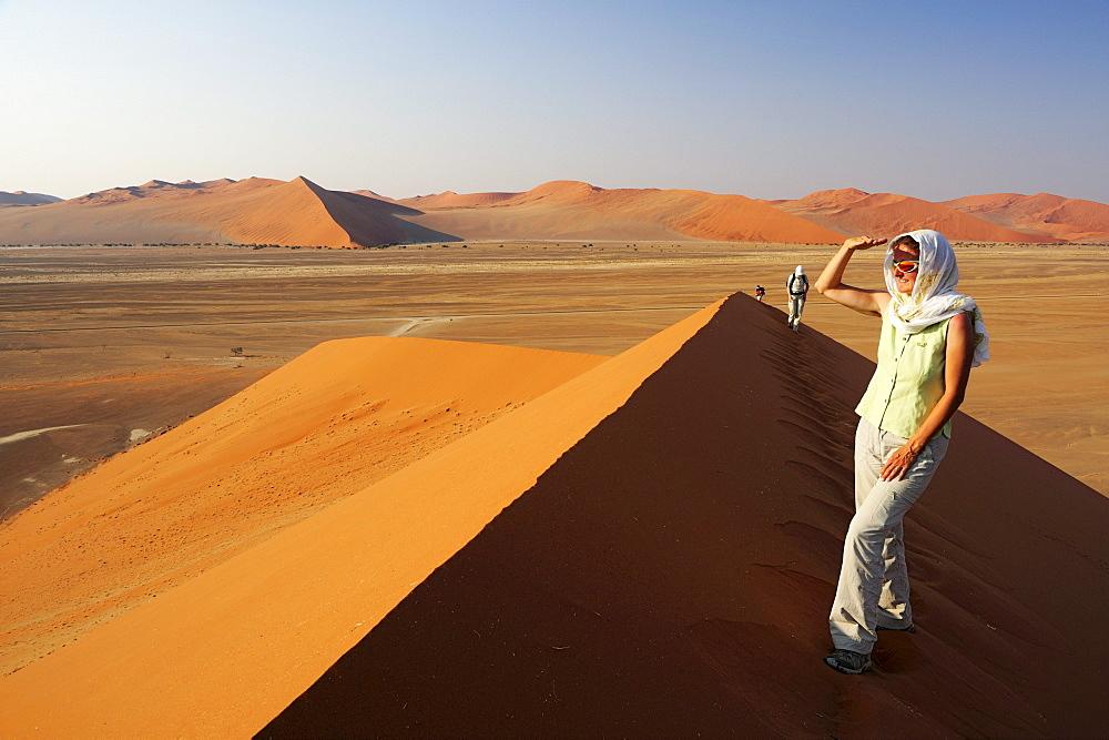 Woman standing on red sand dune and enjoying view in Sossusvlei, dune 45, Sossusvlei, Namib Naukluft National Park, Namib desert, Namib, Namibia
