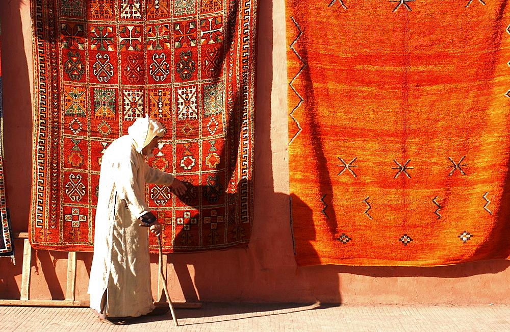 old man walking in front of carpets, Marrakech, Morroco, Africa