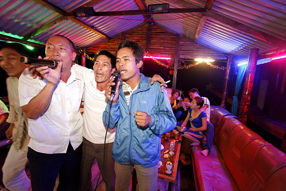 Men singing karaoke on a boat, Halong Bay, Quang Ninh, Vietnam