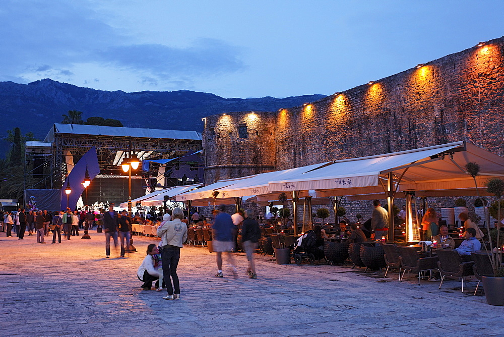 Restaurants along the city wall in the evening, Budva, Montenegro, Europe