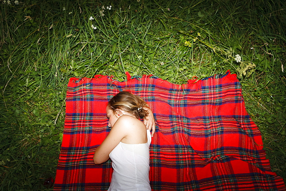Young woman lying on red checked blanket on grass