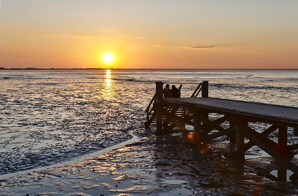 Couple watching the sunset, Schleswig-Holsteinisch Wadden Sea National Park, Husum, Schleswig-Holstein, Germany