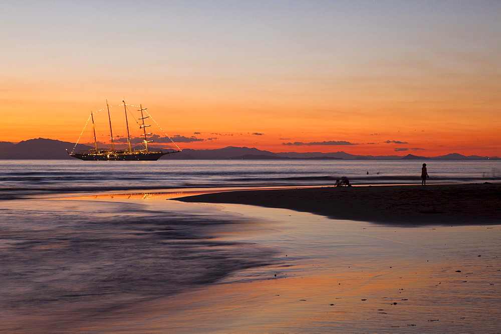 People on beach and sailing cruiseship Star Flyer (Star Clippers Cruises) at sunset, Puerto Caldera, Puntarenas, Costa Rica, Central America, America