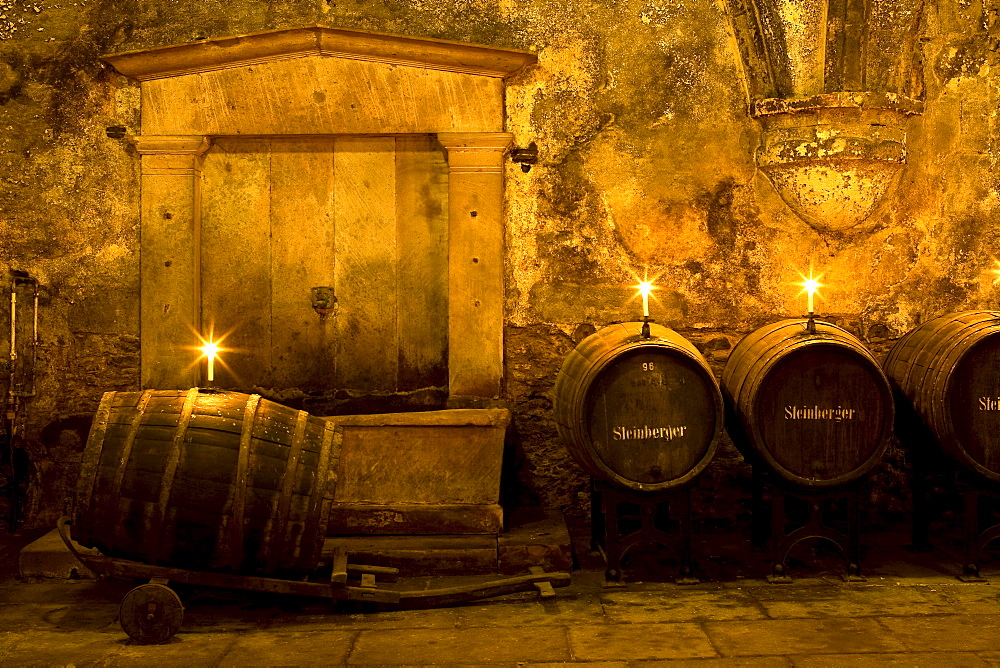 Candlelit barrels inside wine cellar of Eberbach abbey, a medieval monastery at Eltville am Rhein, Rheingau, Hesse, Germany, Europe