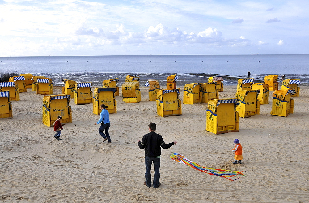 Family playing with a kite on the beach at Cuxhven, North Sea coast of Lower Saxony, Germany