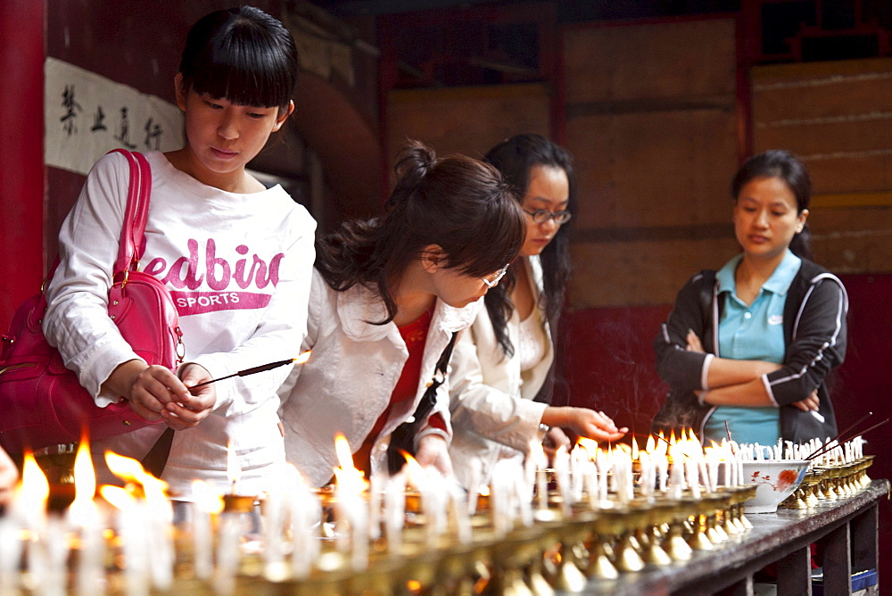 Oil lamps and butter lamps, women lighting candles, buddhist ritual, Luohan Temple, buddhist temple downtown, Chongqing, People's Republic of China