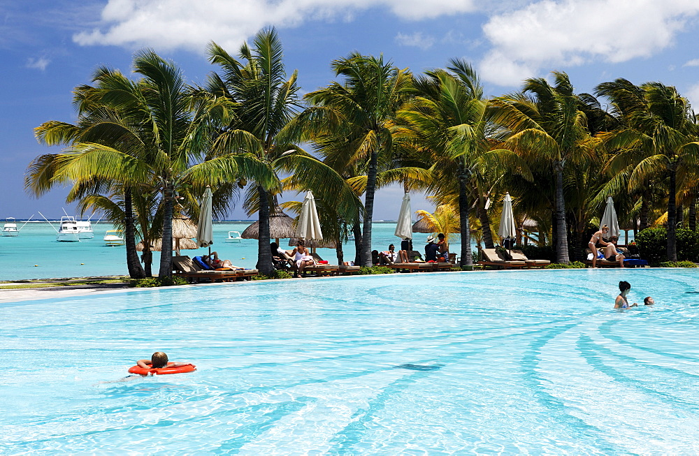 People and palm trees at the pool of Beachcomber Hotel Paradis & Golf Club, Mauritius, Africa