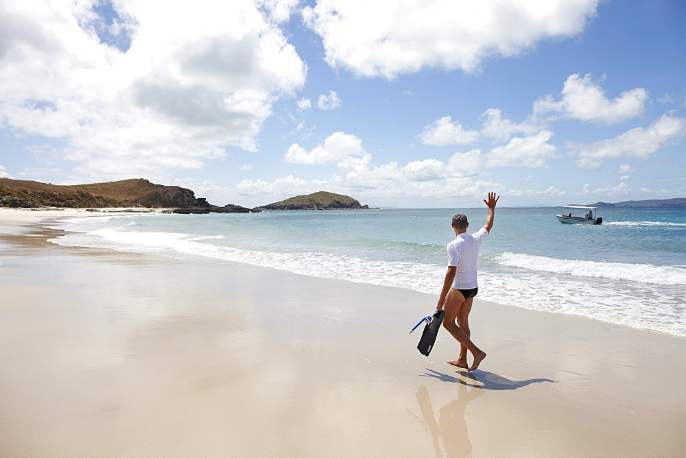 Tourist with snorkelling gear on Middle Island beach, Island next to Great Keppel Island, Great Barrier Reef Marine Park, UNESCO World Heritage Site, Queensland, Australia