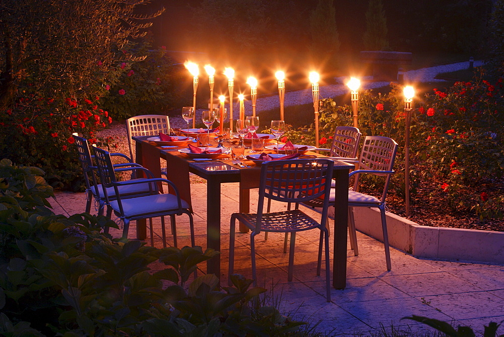 Decorated garden table with flaming torches in the evening light, Bavaria, Germany