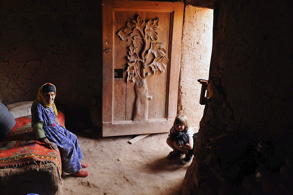 Old Berber woman and young European girl in traditional Berber house with adorned door, Kasbah Ait Benhaddou, Ait Benhaddou, Atlas Mountains, South of the High Atlas, Morocco, Africa