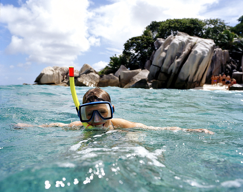 Snorkelling in shallow water over coral reef off tiny Coco Island, La Digue and Inner Islands, Republic of Seychelles, Indian Ocean