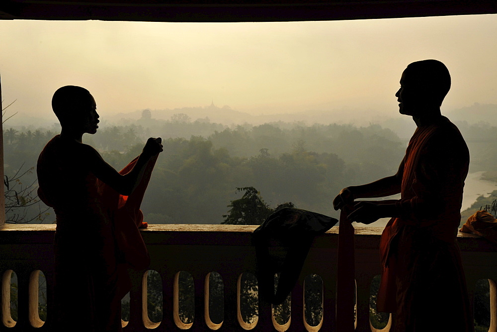Buddhist monks, novices, cladding their robes, view to the East over trees and hills in morning dust, Phu Si hill, Luang Prabang, Laos