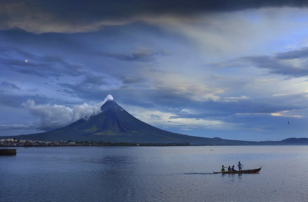 Young people on outrigger with steaming Mayon Volcano, Legazpi City, Luzon Island, Philippines, Asia