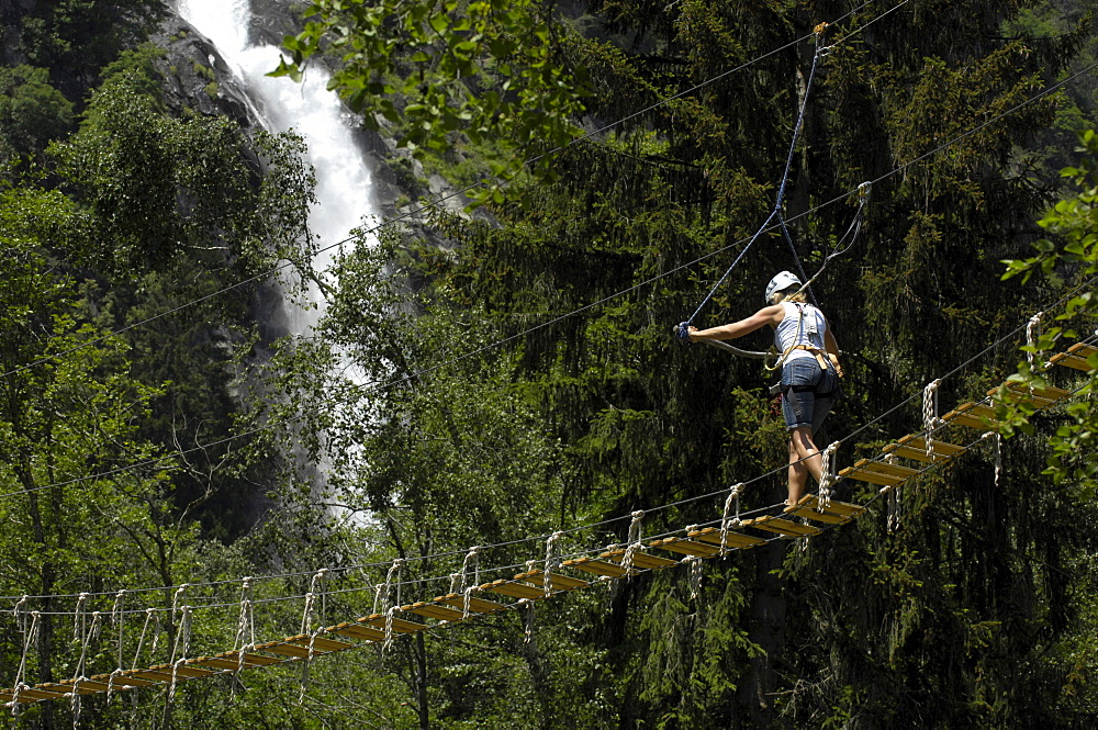 One person on suspension bridge at climbing park, Partschins waterfall in the background, Vinschgau, Alto Adige, South Tyrol, Italy, Europe
