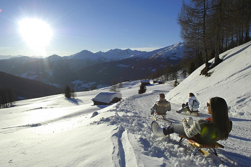 People sledding downhill in snowy mountain scenery, Alto Adige, South Tyrol, Italy, Europe