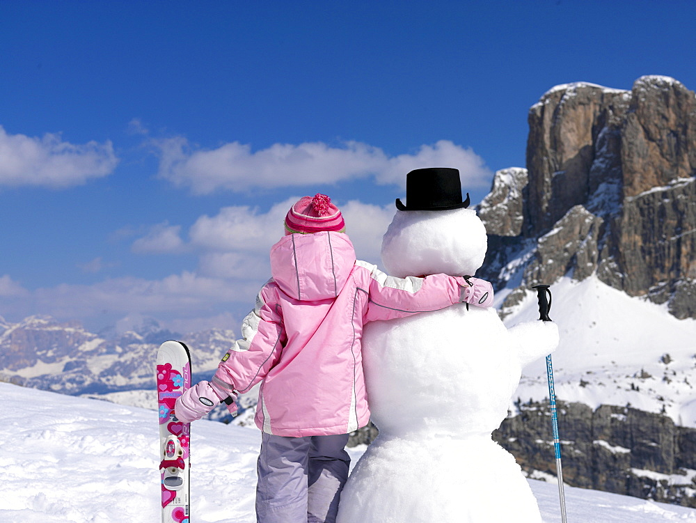 Little girl with skis an snowman, Alto Adige, South Tyrol, Italy, Europe