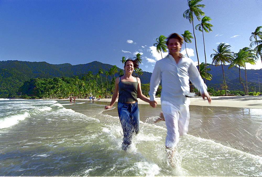 Young couple running hand in hand on the waterfront, Maracas Bay, Trinidad, Caribbean, America - 1113-50286