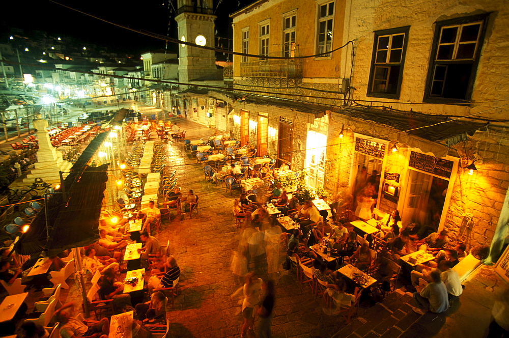 People sitting in front of a bar at the promenade at night, Hydra, Saronic Islands, Greece