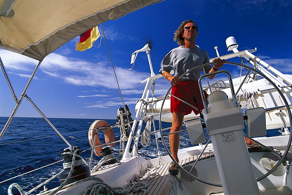 Man behind the wheel of a sailing boat under blue sky, St. Vincent and The Grenadines, Caribbean, America