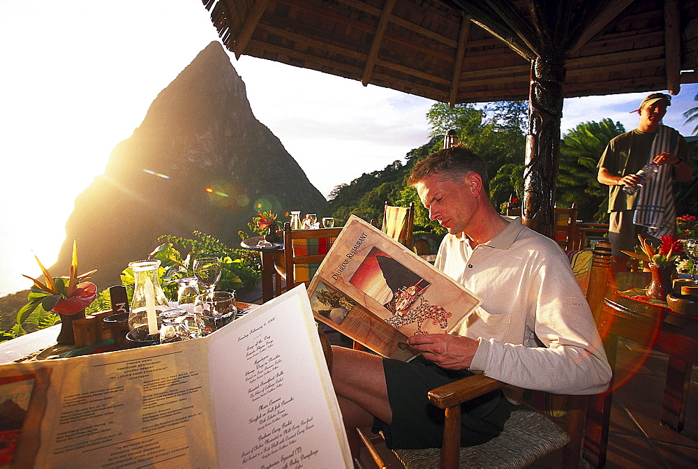 Tourist reading the menu at restaurant Dasheene at Ladera Resort, St. Lucia, Caribbean, America