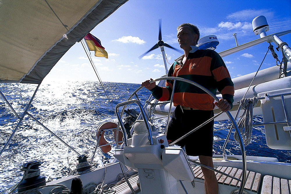 Man behind the wheel of a sailing boat, St. Vincent, Grenadines, Caribbean, America