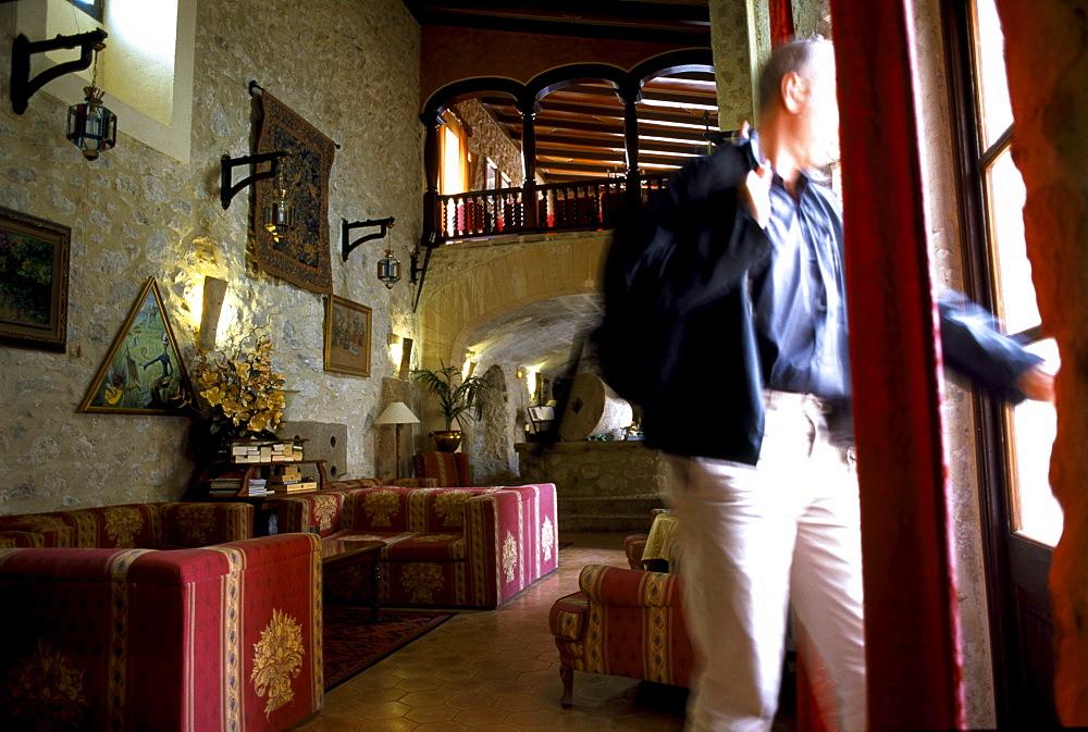 A mature man standing in the parlour of Finca Monnaber Nou, Tramuntura, Majorca, Spain