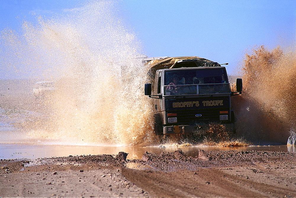 Truck of Fred Brophy's Boxing Troupe driving through water, Outback, Australia