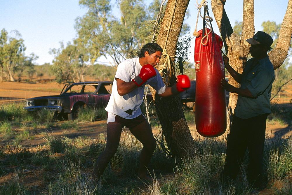 Denny und Paul boxing the sandbag, Fred Brophy's Boxing Troupe, Boulia, Simpson Desert, Australia