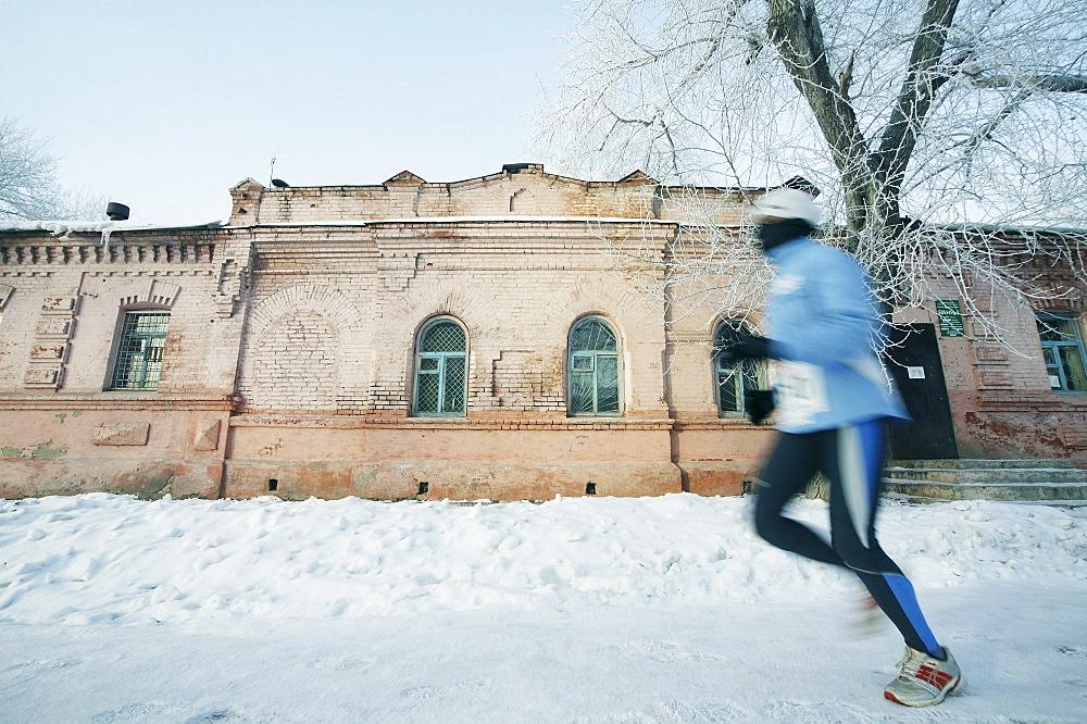 Runner running over snow covered street, Omsk, Siberia, Russia