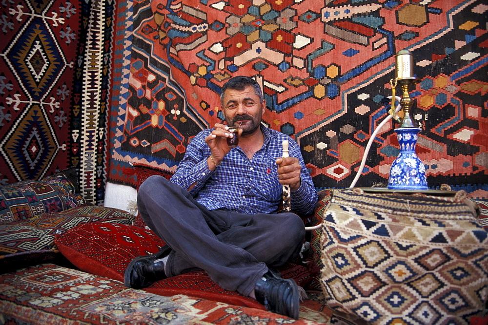 Carpet dealer smoking waterpipe, Antalya, Antalya, Turkey