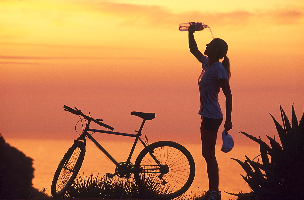 Female mountainbiker cooling herself with water after cycling tour, coastline, Mallorca, Spain