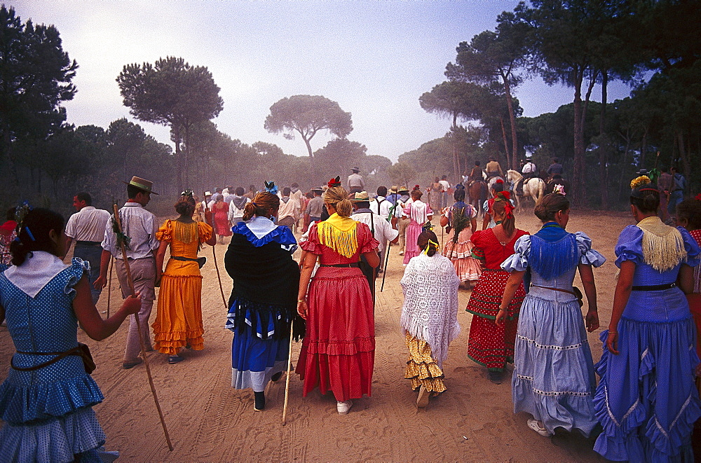 Pilgrims walking along sandy road, Andalusia, Spain
