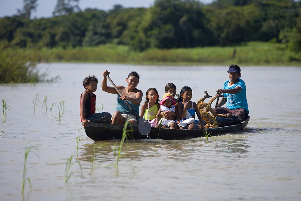 Amazon Indian family in a canoe on a sidearm of the Amazon River, Boca da Valeria, Amazonas, Brazil, South America
