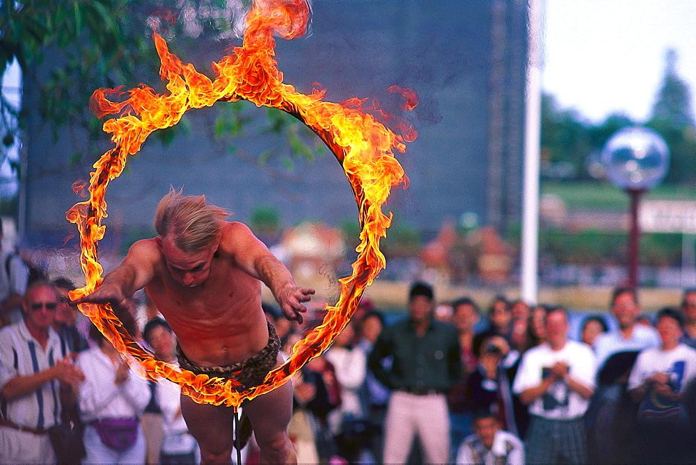 Street artist jumping through a ring of fire, The Rocks, Sydney, NSW, Australia