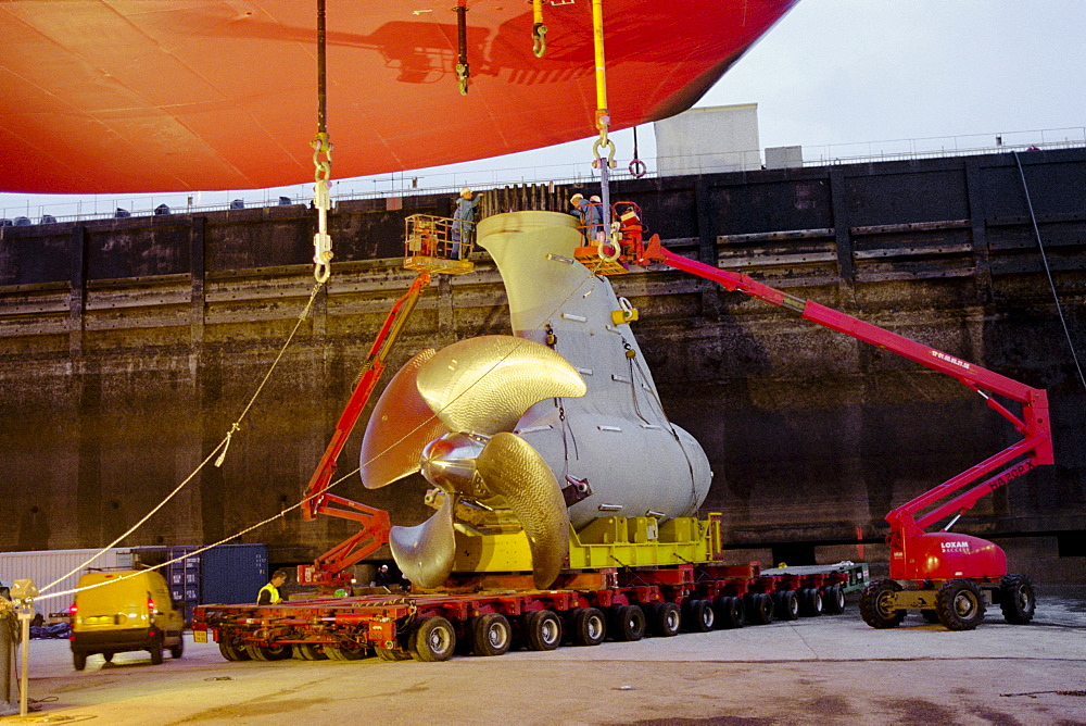 Low loading truck bringing mermaid motor pod, attaching the mermaid motors, dry dock, Queen Mary 2, Saint-Nazaire, France - 1113-59791
