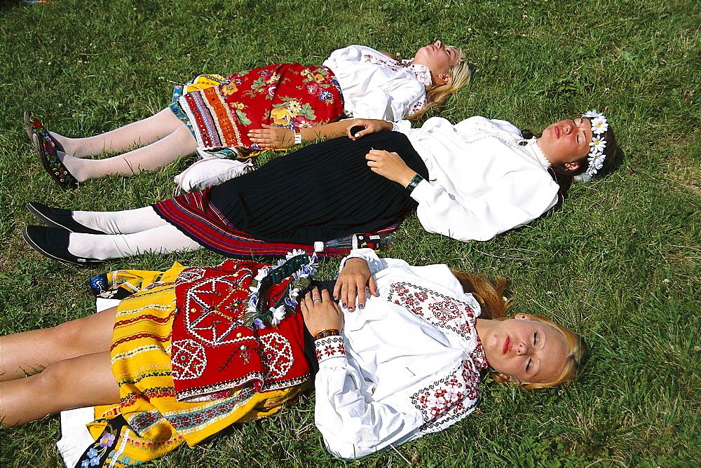 Young women in traditional costumes sunbathing on meadow, traditional celebration, Tallinn, Estonia - 1113-60867