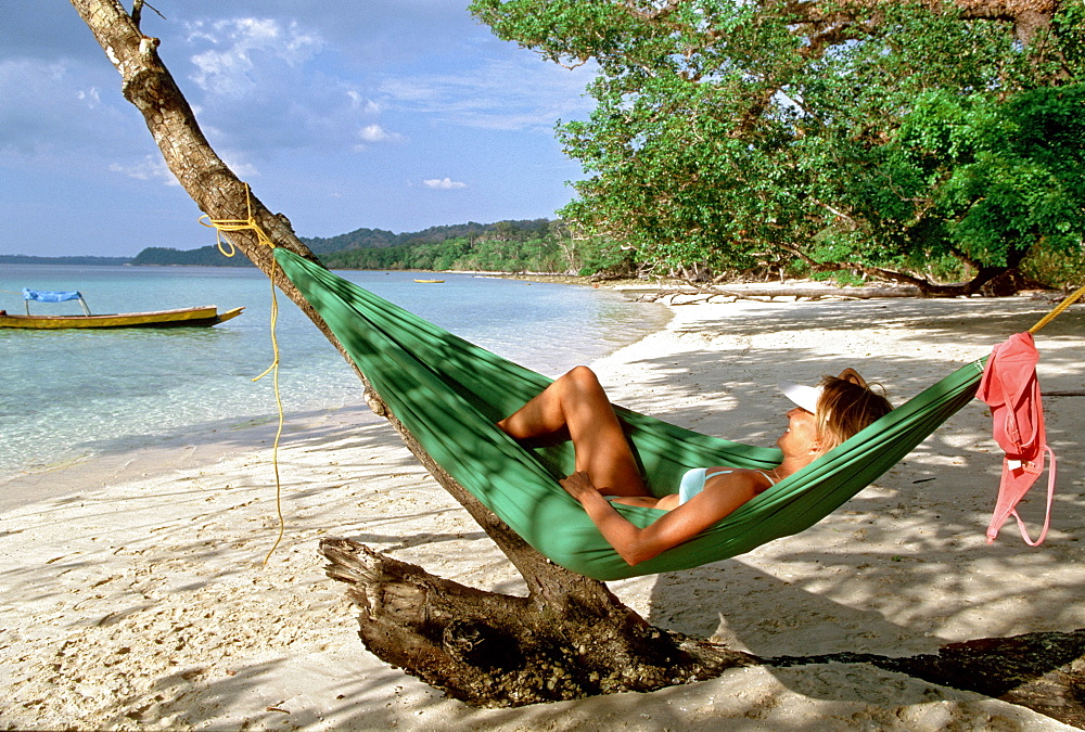 Woman in a hammock on Elephant Beach, Havelock Islands, Andaman Islands, India