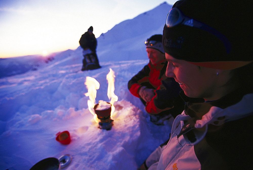 Group of people sitting around a camping stove after a snowshowing tour, Trekking, Nebelhorn, Allgaeuer Alps, Allgaeu, Germany