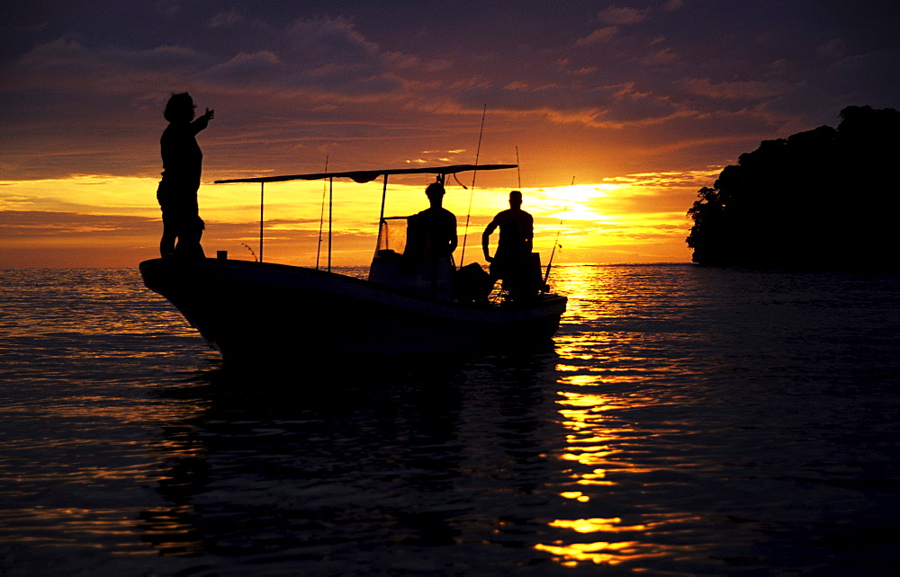 Young people in a boat at sunset, Tallillis, Rabaul, East New Britain, Papua New Guinea, Melanesia, PR